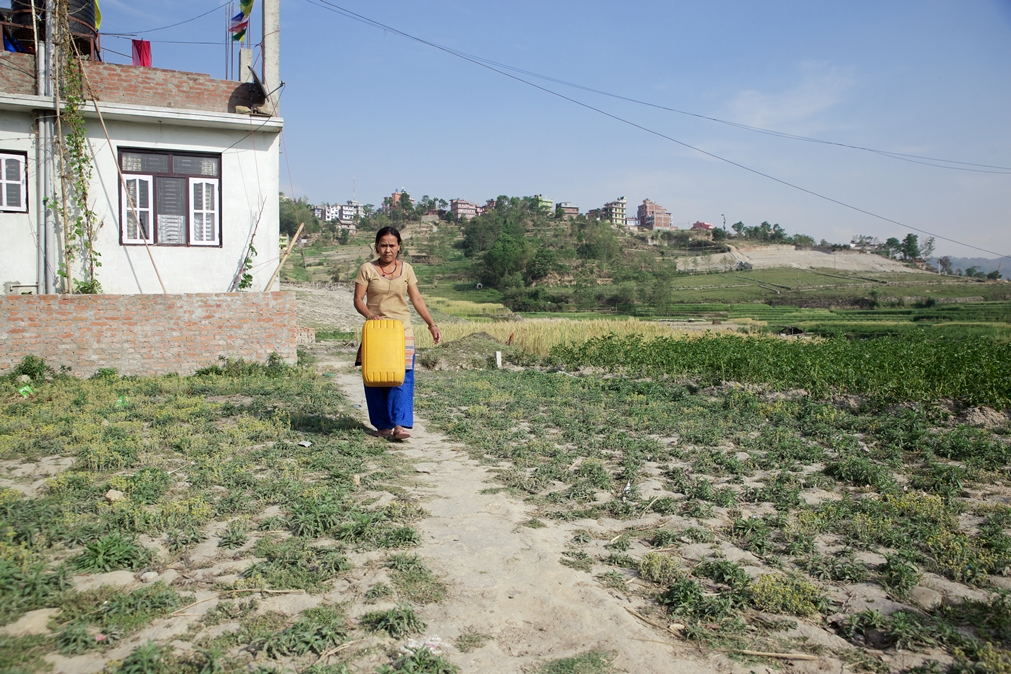 Rasmina's mother, Sanchakumari Tamang, walks to her house after she filling a jerry can with water the nearby well. Photo Credit: Mithila Jariwala
