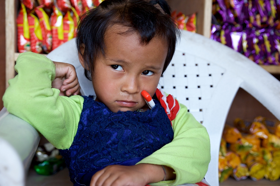 Taking a break from playing, Rasmina Tamang, age 5, sits in her father's shop while a doctor takes her temperature during a follow up visit. Mathila Jariwala / Sabin Vaccine Institute