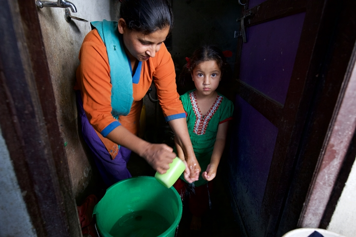 Parvati Puri helping her daughter Jenisha to wash hands before eating. Photo Credit: Mithila Jariwala