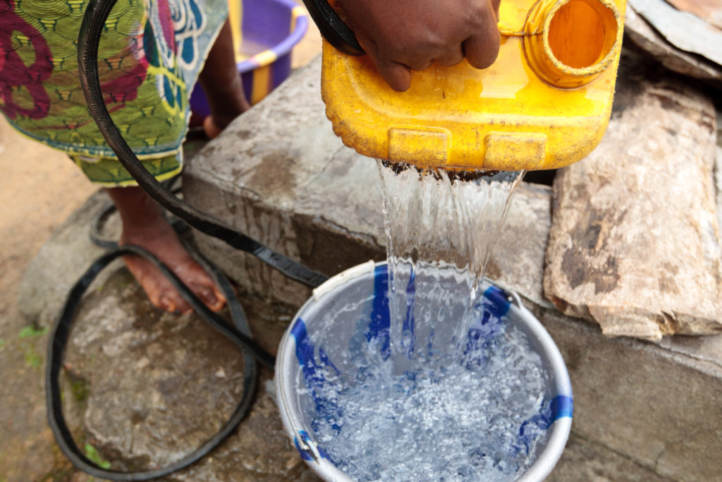 A woman draws water from a well in the town of Masongbo, Sierra Leone on Thursday July 12, 2012.