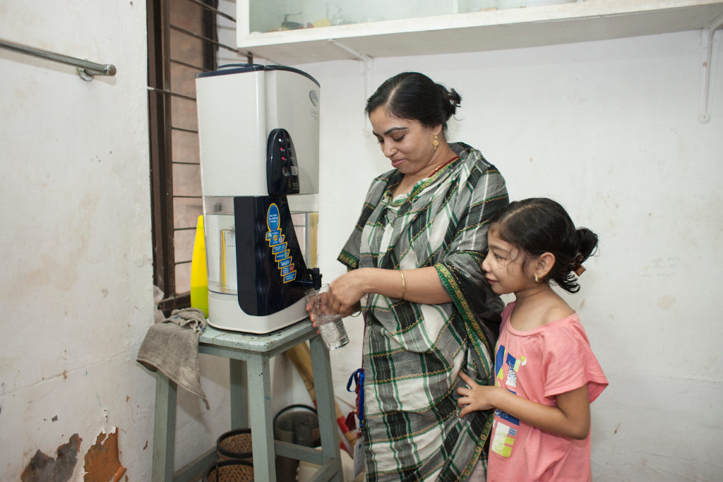 Nishita's mother, Rehana, helps her with a glass of water. The family drinks from a water filter in their household. Photo credit: Suvra Kanti Das