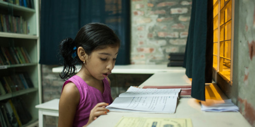 Nishita, out of school due to typhoid, reads a textbook at home. Photo credit: Suvra Kanti Das