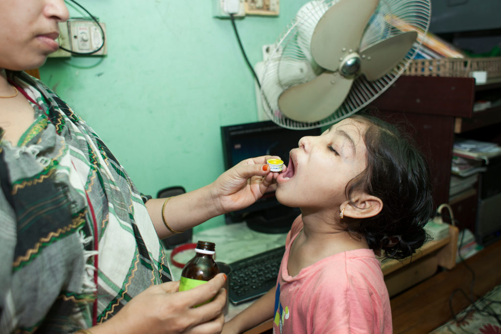 Nishita's mother, Rehana, gives her vitamins to help her stay healthy. Photo credit: Suvra Kanti Das