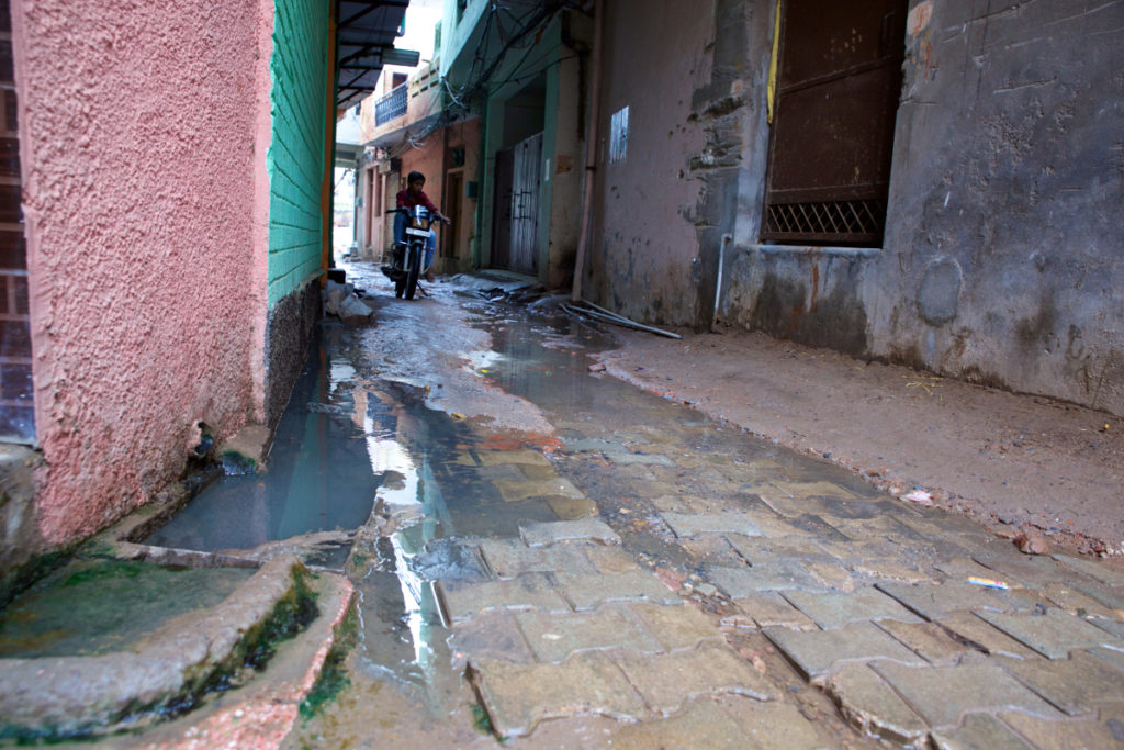 A street in the village of Jharsa contains sewage and dirty water, increasing the risk of typhoid for its inhabitants like Yadav. (Photo credit: Mithila Jariwala)