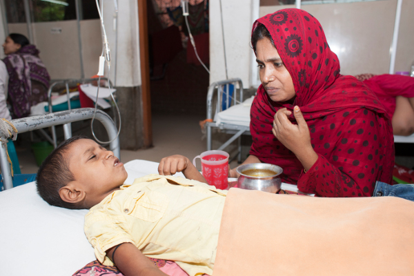 Hasina struggles to convince Samir to take some food and drink. Severe loss of appetite is a common symptom of typhoid.