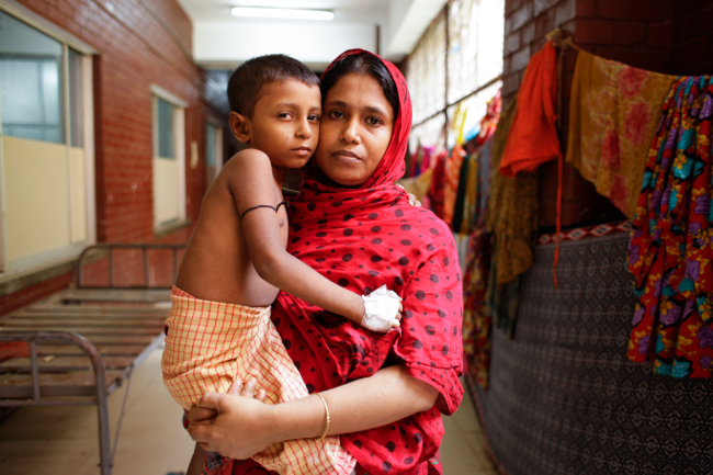 Samir, six, is cradled in the arms of his mother, Hasina Akhter. A housewife, she is now searching for a way to earn money to pay Samir's medical bills.