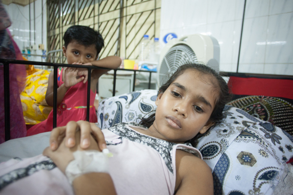 Nurunnahar had to miss school for two weeks with a case of typhoid that sent her to the hospital. One of her younger siblings is seen here watching over her hospital bed.
