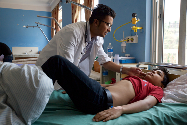 Dr. Asim Shrestha examines his patient, 13-year-old Subigyan Khanal, who has come into Dhulikhel Hospital complaining of fever, weakness and headache.