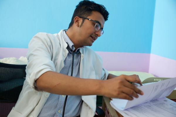 Dr. Shrestha reviews his patient Subigyan's chart.