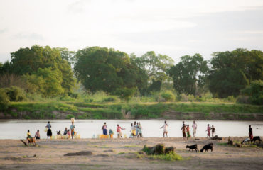 Villagers in Kenya gather at the bank of a river to gather water. When drought causes water sources to run dry, many resort to unsafe water sources.