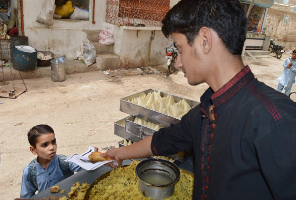 Asim buys samosas, one of his favorite foods, from a street vendor near his house.
