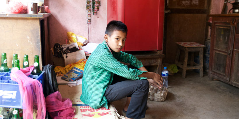 Eleven-year-old Ayush Lama sits in his home. He was the first in his family to get sick with typhoid.