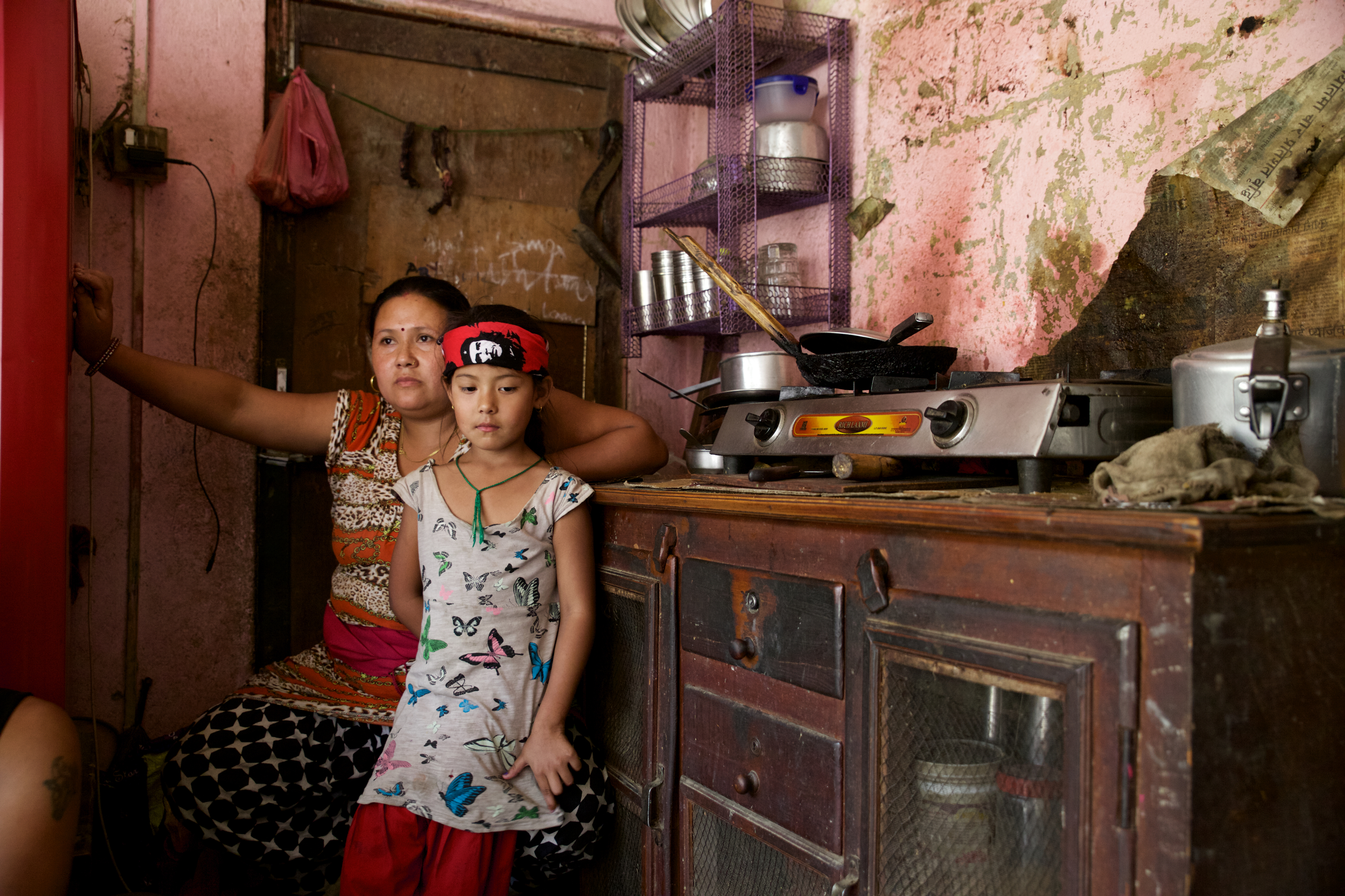 Ayusha sits in the kitchen with her mother, Janu. Like many suspected typhoid cases, Ayusha was never brought to the hospital and did not receive medical care.