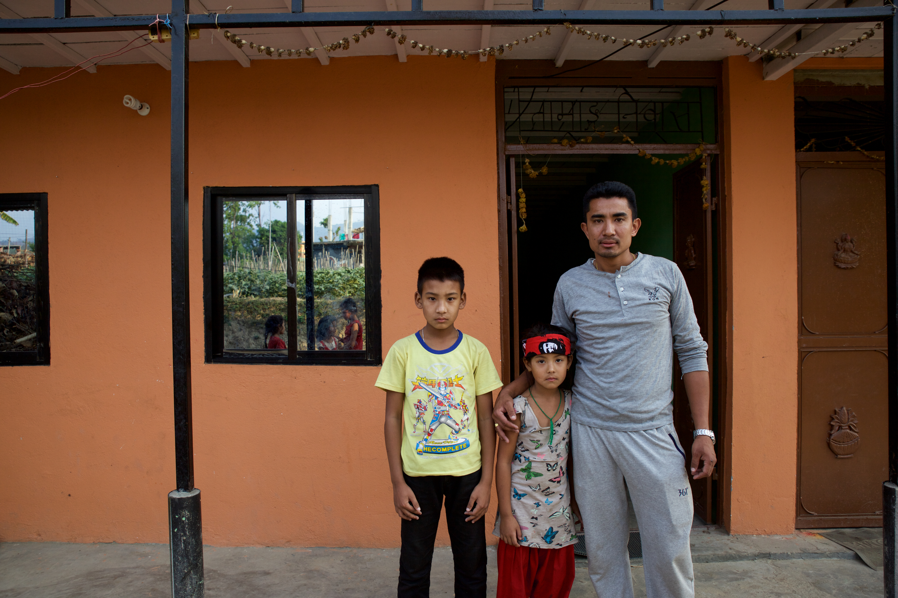 Ayush, Ayusha and Ram in front of their family home. After the devastating 2015 earthquake in Nepal, the Lama family rebuilt their home from wood and stone, taking out a loan to ensure their children were safe from future earthquakes..