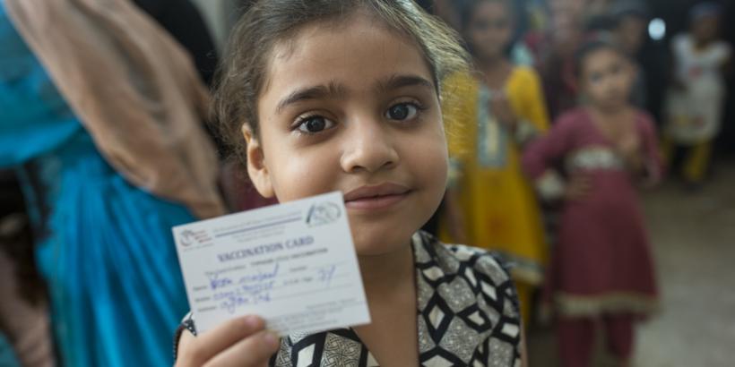 girl holds up immunization card