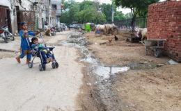 Children play in a street with an open drain in Pakistan. Photo: Raja Khalid Shabbir.