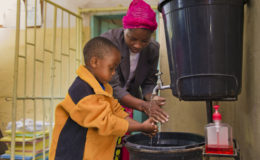 Young boy washes hands at health center in Kafue District, Zambia. PATH/Gareth Bentley