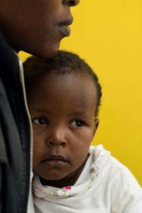 Angela Godfrey, age 26, holds her daughter Sara Kambua, age 5, at the health clinic in Mukuru, Kenya, February 5, 2018.
