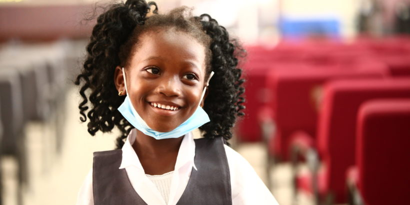 happy child smiles after receiving her typhoid vaccine
