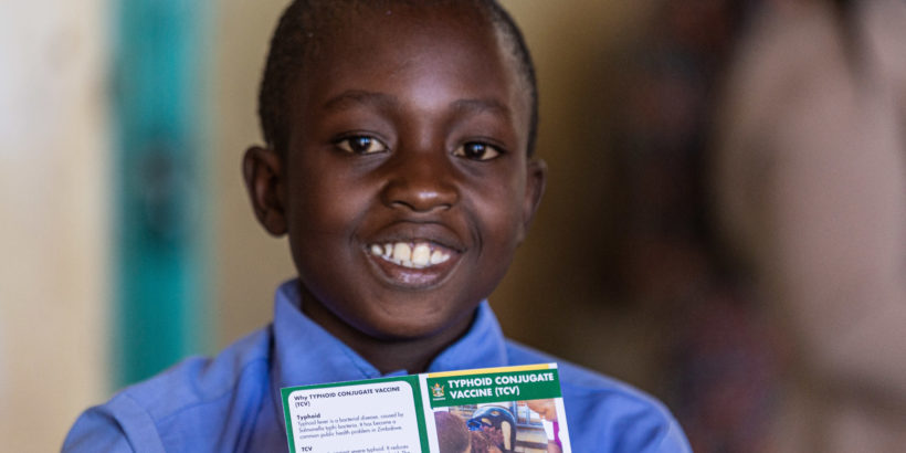 A young boy smiles with his vaccination card after receiving typhoid conjugate vaccine in Zimbabwe