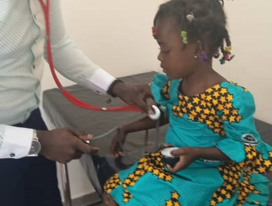 Doctor checks girl's heartrate before administering TCV in Ghana