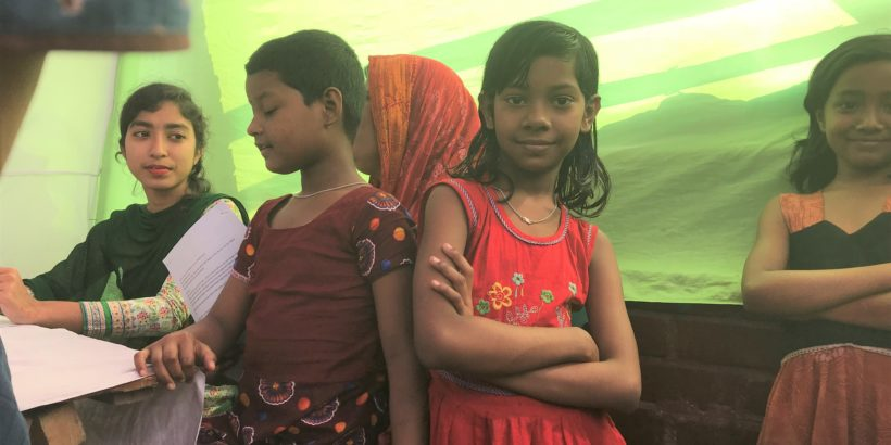 Girl in Bangladesh crosses her arms and looks at the camera